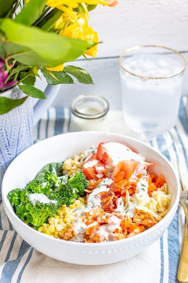 ThisBuffalo Chicken Quinoa Salad is made with spicy shredded buffalo chicken, shredded carrot, chopped celery, tomato, corn, broccoli, bacon, and cheese on a bed of quinoa and spinach. It's a quick, easy, and healthy weeknight meal.
