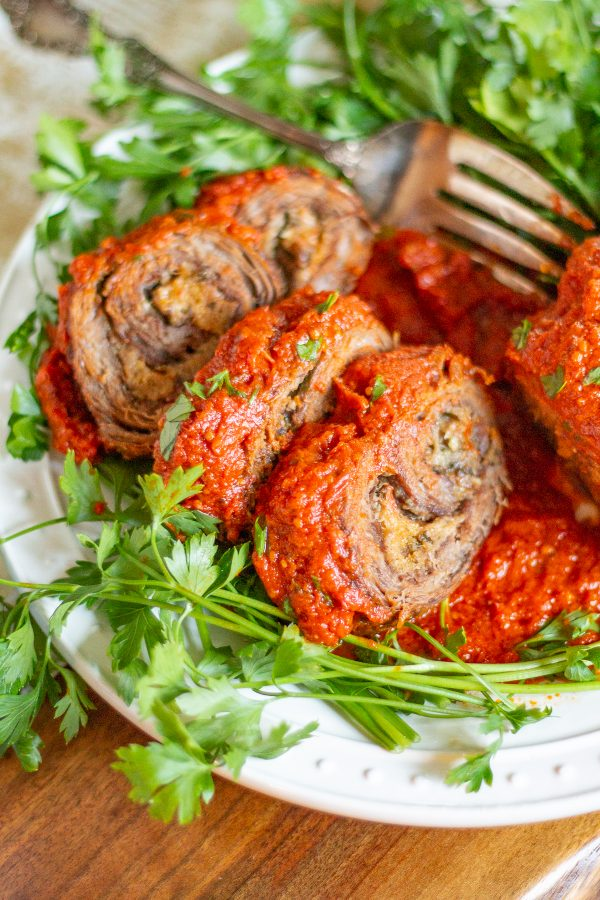 Braciole with a Tomato Sauce | Braciole is a recipe that is perfect for a special occasion that only requires 20 minutes of active preparation time. Flank Steak is topped with cheese, herbs, and breadcrumbs, seared, and then roasted in tomato sauce. Let this recipe for Braciole with tomato sauce be your secret weapon for hosting a dinnerparty.
