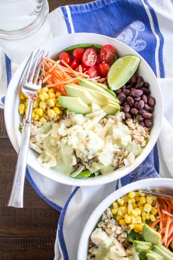 Ranch Chicken Salad Bowl - This meal is loaded with fresh veggies and protein. Chicken is seasoned with ranch dressing mix cooked, and then served with lettuce, rice, black beans, corn, tomatoes, carrots, avocado and cheddar cheese with a poblano cream sauce and fresh lime!