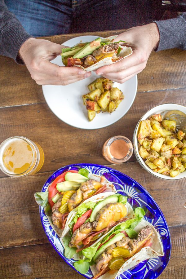 Bacon Cheeseburger Tacos are made with cheeseburger wrapped in flour tortillas and topped with tomato, avocado, bacon, lettuce, pickles, grilled red onion, and a sriracha animal sauce. They are just as crazy delicious as you might imagine.