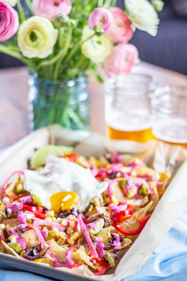 Brussels Sprout Nachos - cheesy nachos topped with roasted brussels sprouts, corn, pickled onions, fresno chilis, a fried egg, and a roasted garlic and beet crema.
