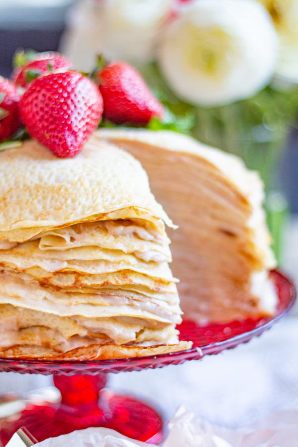 Roasted Strawberry Crepe Cake is made with 25 layers of crepes with roasted strawberry custard spread between each individual layer. The result is a slightly sweet cake that can easily serve 14-16 people. (But maybe less because it is so delicious that people might want seconds).