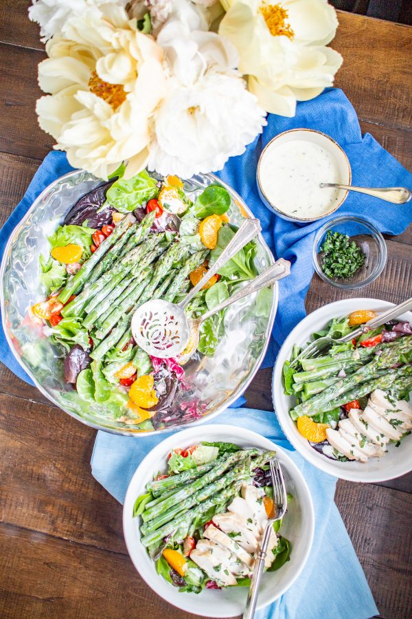 This easy to prepare Asparagus Salad is bursting with fresh flavors. Cooked asparagus, grape tomatoes, mandarin oranges, and red onion are placed on top of mixed greens and then drizzled with a light lemon tarragon yogurt dressing. Serve it as a side dish, or add chicken or salmon to turn it into a complete meal.