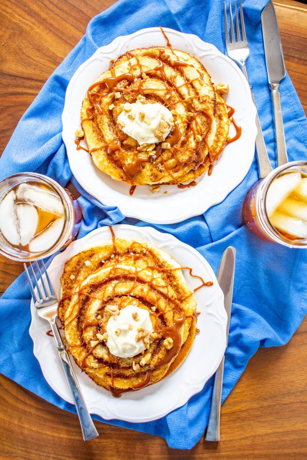 These decadent Cinnamon Roll Pancakes are made with vanilla cake batter swirled with cinnamon sugar, and topped with toffee sauce and cream cheese frosting. They are an over-the-top treat to serve for a birthday or special occasion.