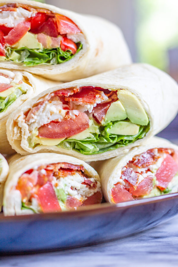 BLT Wraps | The classic BLT gets an upgrade with this easy recipe for BLT Wraps with Avocado and Mozzarella. This is the perfect low-fuss summertime meal. Crispy bacon gets paired with juicy tomatoes, fresh lettuce, slices of avocado, creamy fresh mozzarella cheese, and a touch of mayonnaise. It is a medley of well-loved ingredients, and a perfect way to serve ripe end-of-summer tomatoes. When my friend was hosting a picnic in Lincoln Park, I wanted to bring one of my favorite summertime foods, the BLT. Instead of just adding bacon, lettuce, and tomato, I also added in some shredded fresh mozzarella, and some slices of avocado. And since BLTs have a tendency to fall apart, I made BLT wraps so that I could add more ingredients without worrying about the sandwiches falling apart. I love this recipe because it is easy to make enough to serve a crowd. The only cooking involved in this recipe is cooking the bacon, which can easily be done in large batches. Once the bacon is ready, you can assemble enough wraps to feed the whole family in just 10 minutes. The easiest way to prepare the bacon is to bake it on a sheet pan. While the bacon is cooking, chop the tomatoes, wash the lettuce, grate the mozzarella, and slice the avocado. Once the bacon has cooked, let it cool and then assemble the BLT Wraps. I like to let the bacon cool so that way it doesn't melt the mozzarella. I recommend making these BLT Wraps just before serving, otherwise, the juicy tomato might make the wrap and bacon soggy. And, use the largest tortillas that you can find. I like to buy the Burrito Grande size since they are just the right size to hold lots of ingredients. I am not going to get into specific proportions in the recipe, you can make these BLT Wraps however you like - I recommend preparing 2-3 slices of bacon per wrap. How to make BLT Wraps with Avocado and Mozzarella: Bacon Tomatoes Avocado Lettuce Fresh Mozzarella Mayonnaise Large Tortillas Begin by preparing the bacon. Line a baking sheet with aluminum foil, and lay the bacon out in a single layer. Bake at 375 degrees for about 15 minutes, until the bacon is crispy. Place the cooked bacon on paper towels and blot the excess grease. While the bacon is cooking, chop the tomatoes, slice the avocado, wash the lettuce, and grate or slice the mozzarella. To assemble the wraps, spread some mayonnaise in the center of a tortilla. I use about a teaspoon per tortilla. Then add 2-3 slices of bacon, some chopped tomatoes, sliced avocado, mozzarella, and lettuce. Fold the sides of the tortilla over, and then roll the wrap up. Continue making as many wraps as you like. Slice them in half and serve.