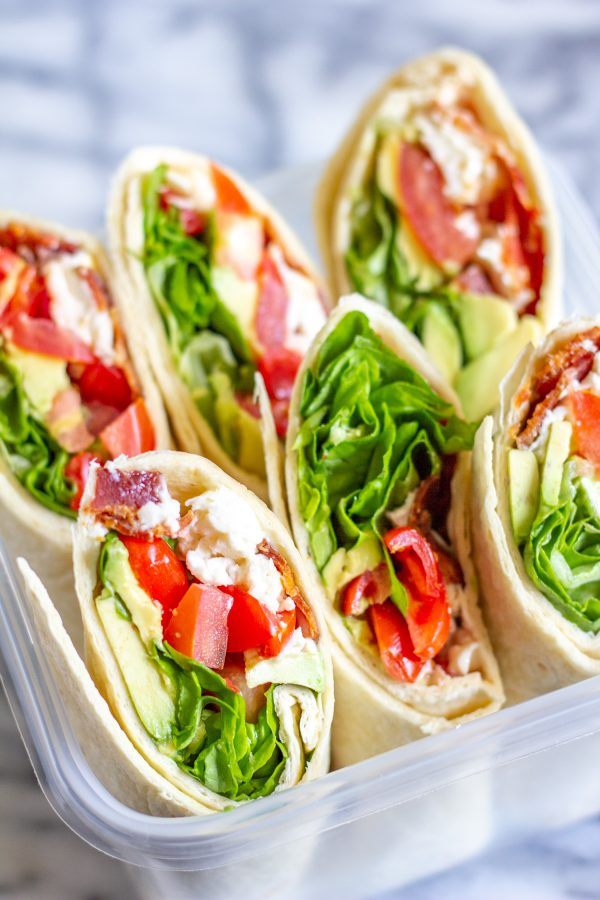 The classic BLT gets an upgrade with this easy recipe for BLT Wraps with Avocado and Mozzarella. This is the perfect low-fuss summertime meal. Crispy bacon gets paired with juicy tomatoes, fresh lettuce, slices of avocado, creamy fresh mozzarella cheese, and a touch of mayonnaise. It is a medley of well-loved ingredients, and a perfect way to serve ripe end-of-summer tomatoes. When my friend was hosting a picnic in Lincoln Park, I wanted to bring one of my favorite summertime foods, the BLT. Instead of just adding bacon, lettuce, and tomato, I also added in some shredded fresh mozzarella, and some slices of avocado. And since BLTs have a tendency to fall apart, I made BLT wraps so that I could add more ingredients without worrying about the sandwiches falling apart. I love this recipe because it is easy to make enough to serve a crowd. The only cooking involved in this recipe is cooking the bacon, which can easily be done in large batches. Once the bacon is ready, you can assemble enough wraps to feed the whole family in just 10 minutes. The easiest way to prepare the bacon is to bake it on a sheet pan. While the bacon is cooking, chop the tomatoes, wash the lettuce, grate the mozzarella, and slice the avocado. Once the bacon has cooked, let it cool and then assemble the BLT Wraps. I like to let the bacon cool so that way it doesn't melt the mozzarella. I recommend making these BLT Wraps just before serving, otherwise, the juicy tomato might make the wrap and bacon soggy. And, use the largest tortillas that you can find. I like to buy the Burrito Grande size since they are just the right size to hold lots of ingredients. I am not going to get into specific proportions in the recipe, you can make these BLT Wraps however you like - I recommend preparing 2-3 slices of bacon per wrap. How to make BLT Wraps with Avocado and Mozzarella: Bacon Tomatoes Avocado Lettuce Fresh Mozzarella Mayonnaise Large Tortillas Begin by preparing the bacon. Line a baking sheet with aluminum foil, and lay the bacon out in a single layer. Bake at 375 degrees for about 15 minutes, until the bacon is crispy. Place the cooked bacon on paper towels and blot the excess grease. While the bacon is cooking, chop the tomatoes, slice the avocado, wash the lettuce, and grate or slice the mozzarella. To assemble the wraps, spread some mayonnaise in the center of a tortilla. I use about a teaspoon per tortilla. Then add 2-3 slices of bacon, some chopped tomatoes, sliced avocado, mozzarella, and lettuce. Fold the sides of the tortilla over, and then roll the wrap up. Continue making as many wraps as you like. Slice them in half and serve.