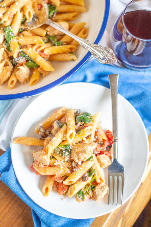 Creamy Tomato Penne with Chicken | My Creamy Tomato Penne recipe is so easy and so delicious. It is the type of meal that comes together quickly and feeds the entire family. Penne pasta is served with a creamy tomato sauce along with diced tomatoes, tender diced chicken breast, mushrooms and spinach. It is a 30 minute recipe that I make again and again.