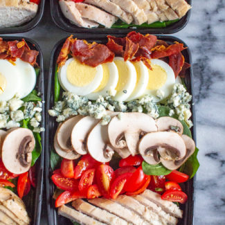 The Best Spinach Salad | A spinach salad topped with chicken breasts, tomatoes, thinly sliced mushrooms, crumbled blue cheese, hard boiled egg, and crispy prosciutto. Perfect for meal prepping.