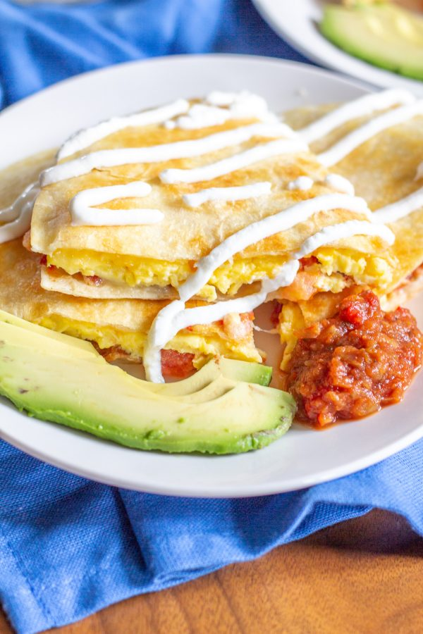 Breakfast Quesadillas have become our favorite weekend breakfast. This meal combines cheesy scrambled eggs with crispy bacon and fresh tomatoes inside crispy tortillas. Serve the quesadillas sliced into triangles with salsa, guacamole, and/or sour cream for dipping.