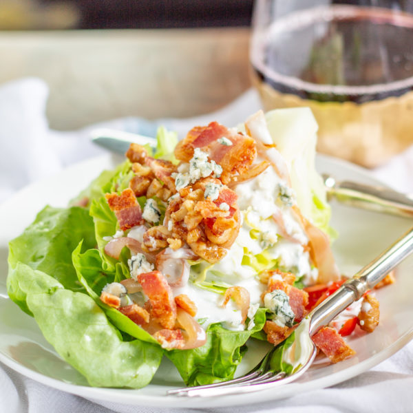 The Best Wedge Salad | A wedge salad is topped with maple toasted walnuts, thick cut bacon, grape tomatoes, caramelized shallots, and homemade chunky blue cheese dressing.