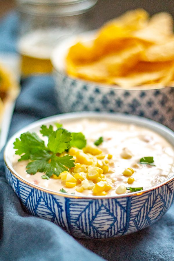Corn Queso | This creamy cheesy corn queso is loaded with fresh steamed corn, tomatoes, and green chilies. #queso #dip