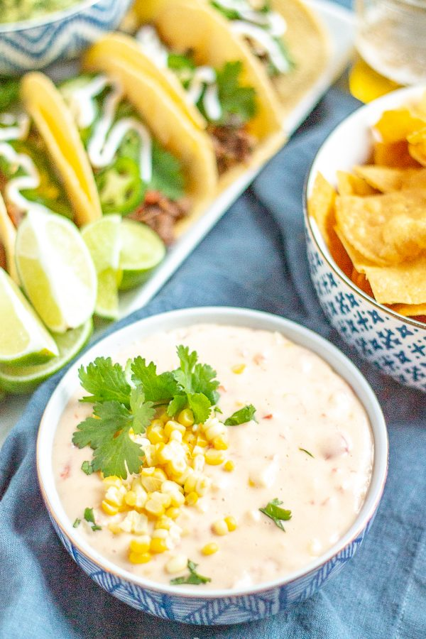 Corn Queso | This creamy cheesy corn queso is loaded with fresh steamed corn, tomatoes, and green chilies.