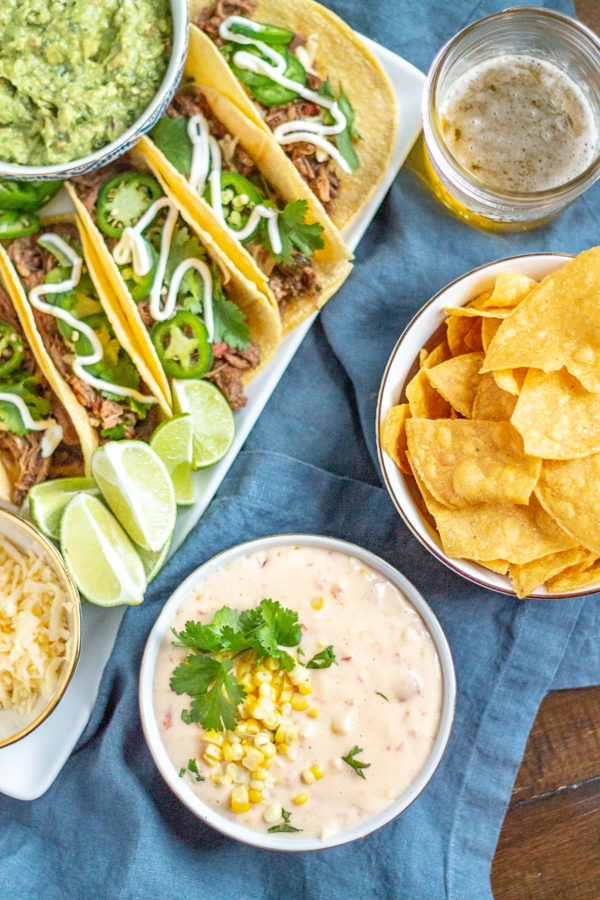 Slow Cooker Shredded Beef Tacos | Slow cooker shredded beef tacos are made with corn tortillas filled with tender spicy shredded beef and topped with cheese, jalapenos, cilantro, and sour cream. This is a zero fuss meal that can feed the whole family with only minutes of active preparation time. #tacos #beef