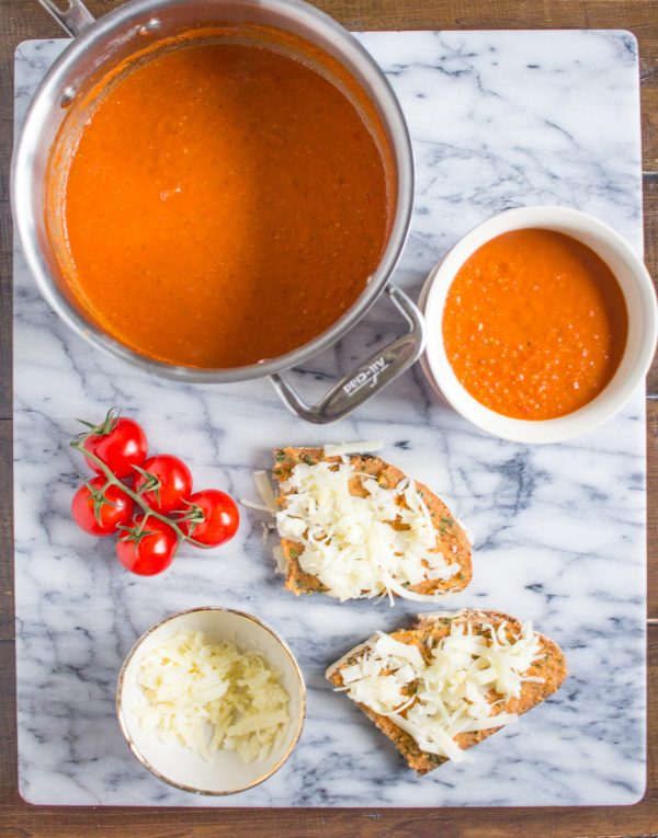 Tomato Soup with Cheesy Toast | This recipe is a new way to serve a classic meal. Tomato soup and grilled cheese belong together. Instead of serving a sandwich with my tomato soup, I served my tomato soup with cheesy toast on top. #soup
