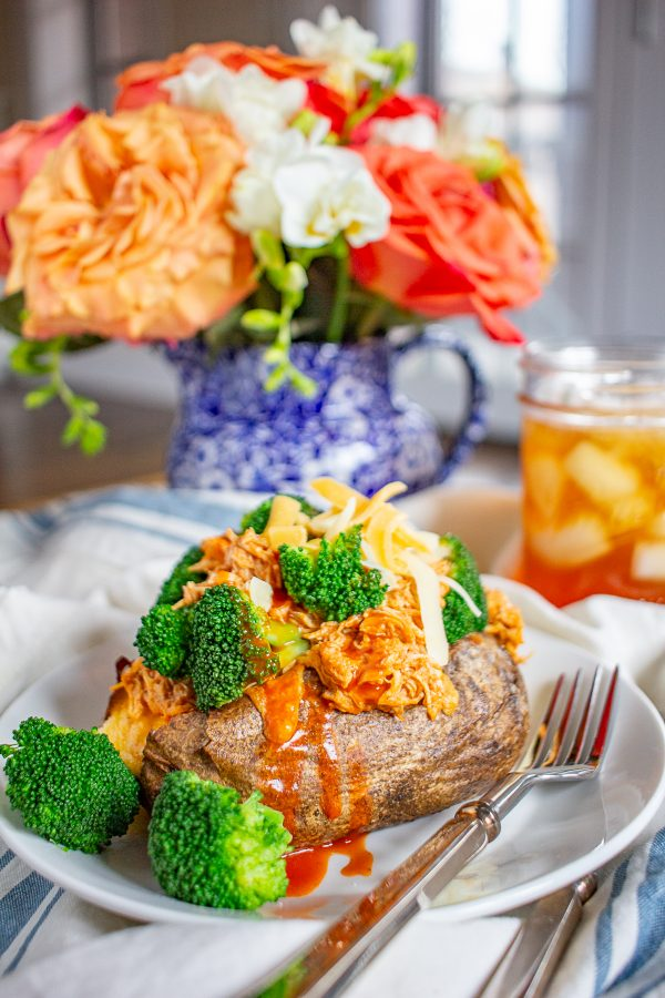 Buffalo Chicken Loaded Baked Potato Recipe | Buffalo chicken loaded baked potatoes are made with cheesy twice baked potatoes topped with shredded buffalo chicken and broccoli.