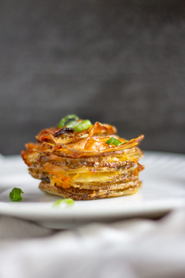 Bacon Cheddar Ranch Potato Stacks are thin slices of potato seasoned with dry ranch dressing and layered with cheddar cheese and bacon.