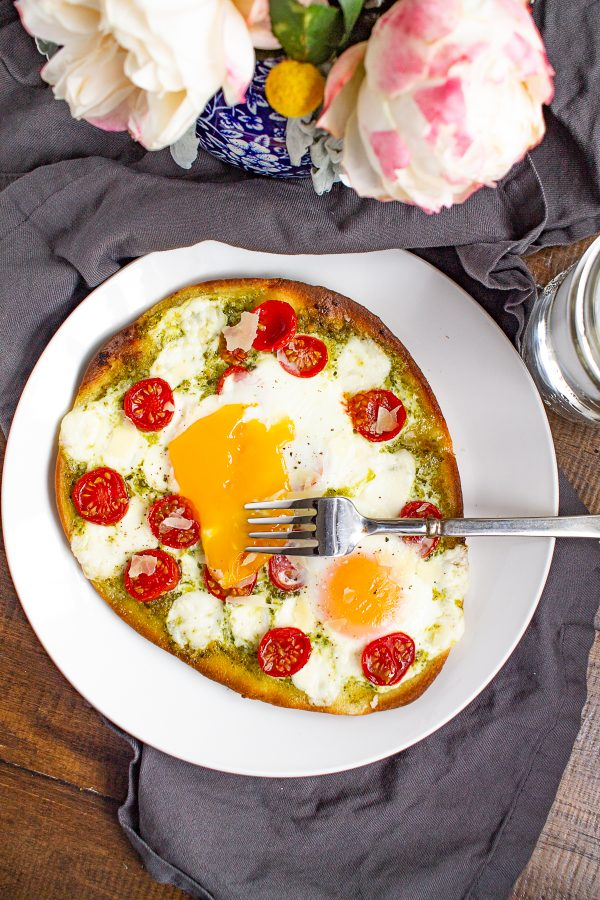Breakfast pizza is a delicious homemade breakfast that can be made in under 20 minutes. Frozen naan gets topped with pesto, tomato, cheese, and eggs for a simple meal.