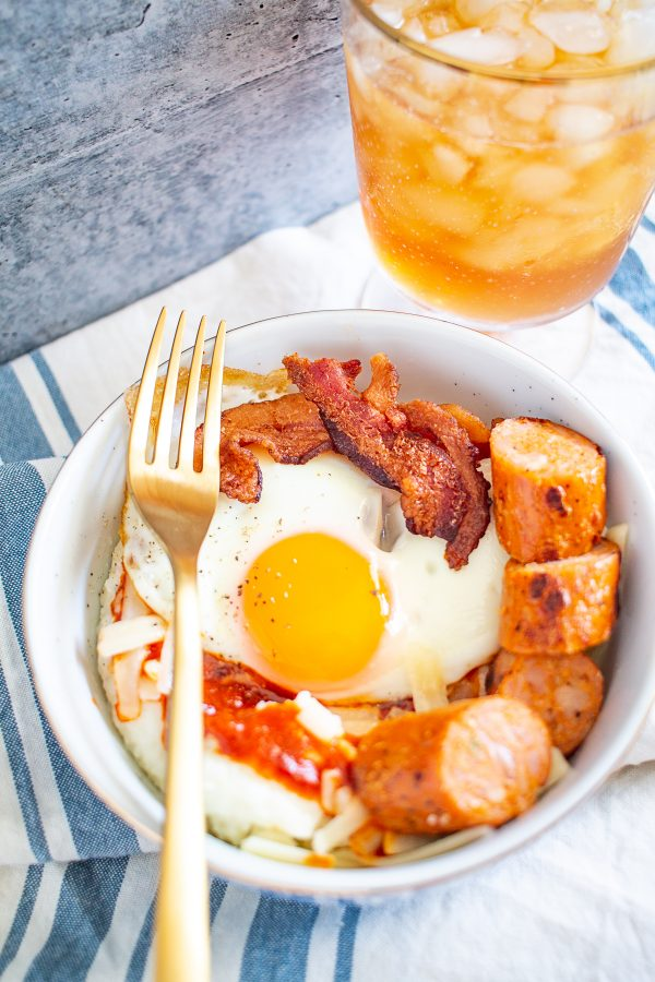 Grits Breakfast Bowl | Creamy cheddar grits are topped with an egg, bacon, sausage, and red chile sauce