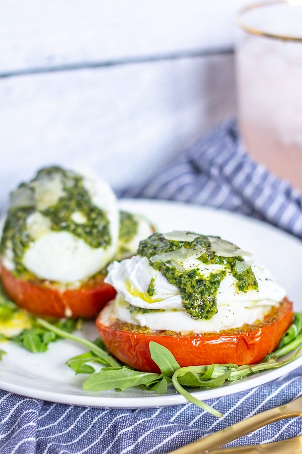 Caprese Eggs Benedict is an easy to make twist on traditional Eggs Benedict made with roasted tomatoes, mozzarella, pesto, and poached eggs. It's one of my favorite breakfasts to make at home over the weekend.