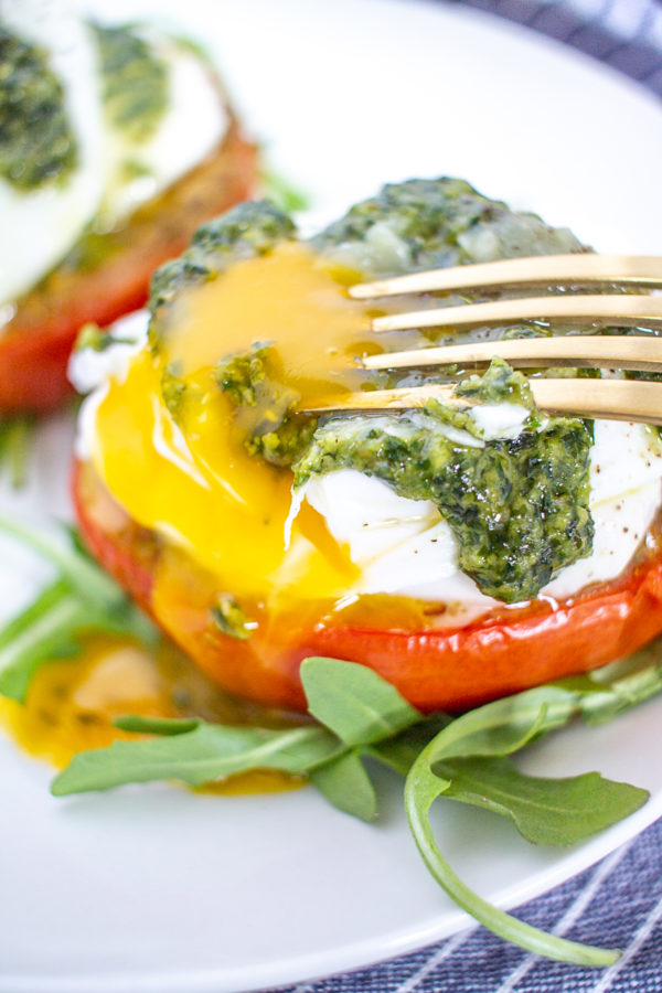 Caprese Eggs Benedict is an easy to make twist on traditional Eggs Benedict made with roasted tomatos, mozzarella, pesto, and poached eggs. It's one of my favorite breakfasts to make at home over the weekend.
