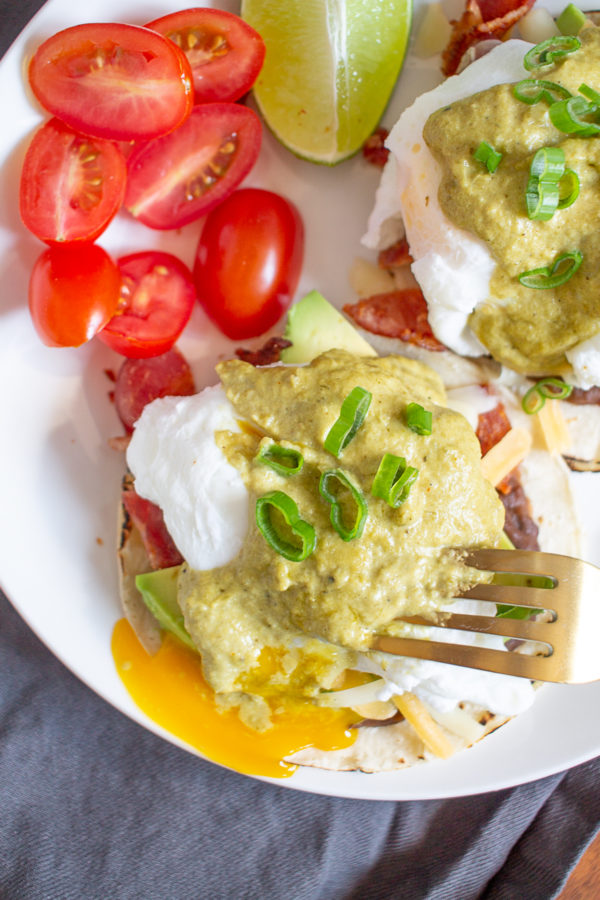 Mexican Eggs Benedict consists of poached eggs, crumbled bacon, cheddar cheese, slices of avocado, and refried beans on flour tortillas topped with poblano cream sauce. It's an extra special breakfast you can make at home.