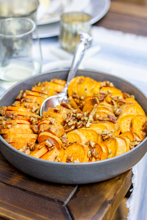 These Maple Pecan Sweet Potatoes are made with sliced sweet potatoes that are roasted in butter, salt, and maple syrup, which are topped with a butter, brown sugar, and pecan topping. It's a sweet and salty side dish perfect for Thanksgiving.