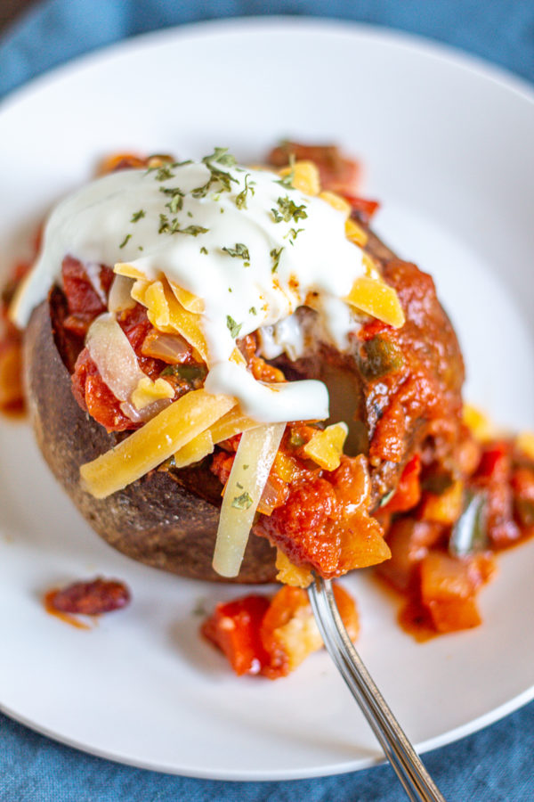 Chili Potatoes are baked potatoes filled with chili and topped with sour cream and cheddar cheese. It's a simple way to serve leftover chili that makes it feel like a whole new meal.