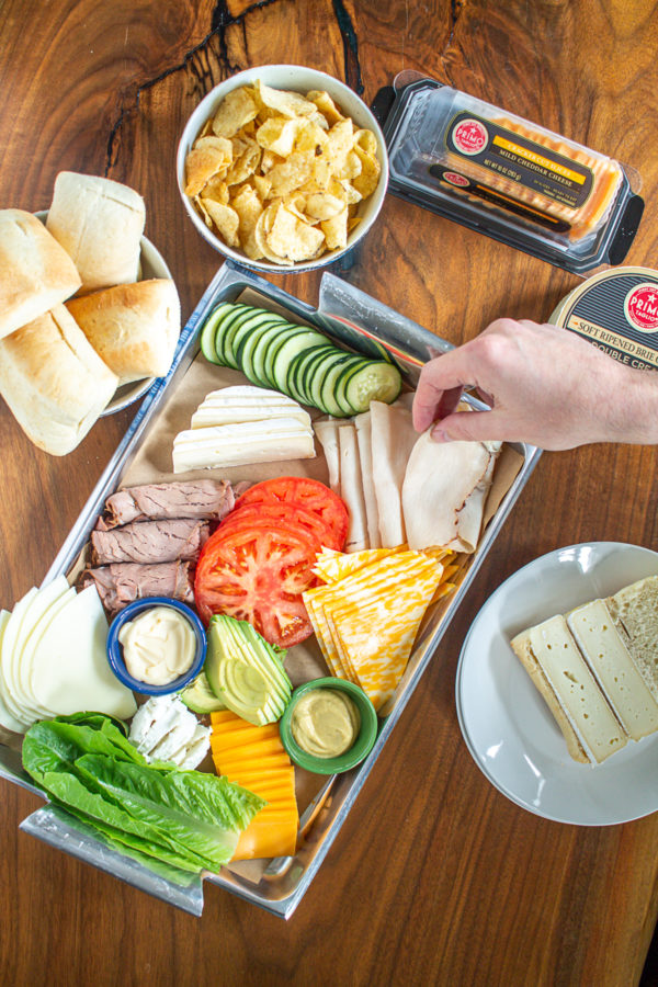Learn how to create a Build Your Own Sandwich Board! Similar to a charcuterie board a sandwich board is filled with meats, cheeses, veggies, and condiments!